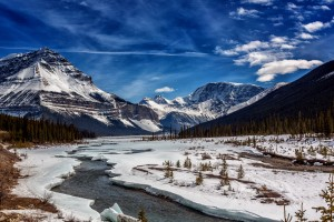 "Driving south along Hwy 93 [we just call the parkway} just before Tangle River Falls in Jasper National Park Canada. Looking South toward ""the Twins"" the ""rim"" of the Athabasca Glassier. Winter is all but given up all that lest is for the snow to melt. All fine Art Landscape and other images are available as art prints in collections and as limited edition signed copies. All canvas prints are all limited edition and signed. No modification, cropping or further editing is permitted with out with the expressed permission of Drew May Photography."